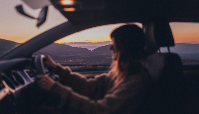 Girl driving car during a beautiful sunset