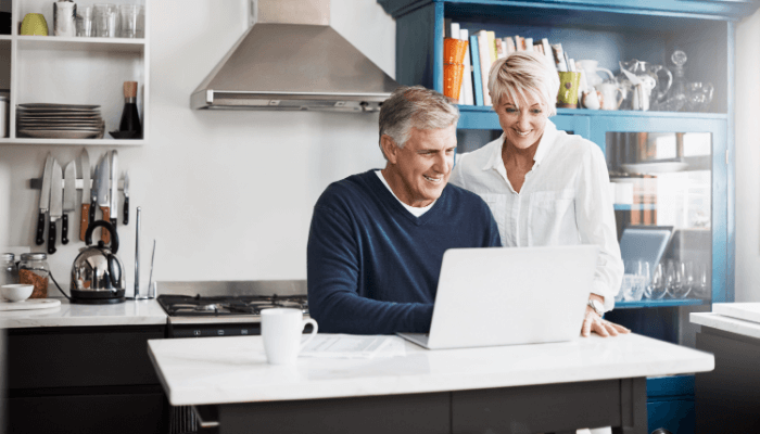 Older couple looking at laptop on kitchen bench