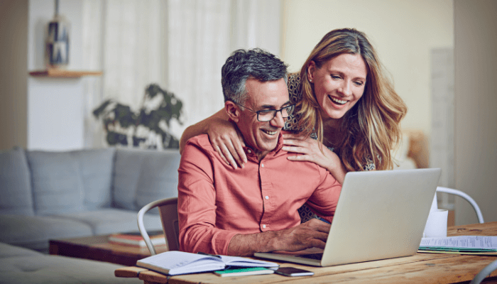 Older couple looking at computer and laughing