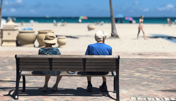 Older couple sitting on bench at the beach
