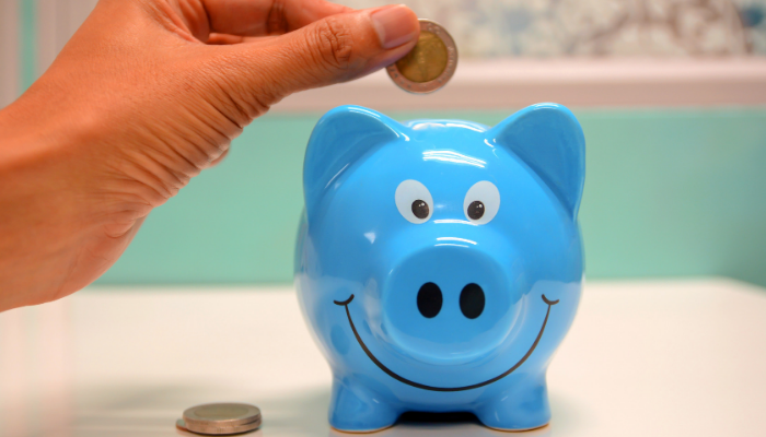 Person holding coin above piggy bank