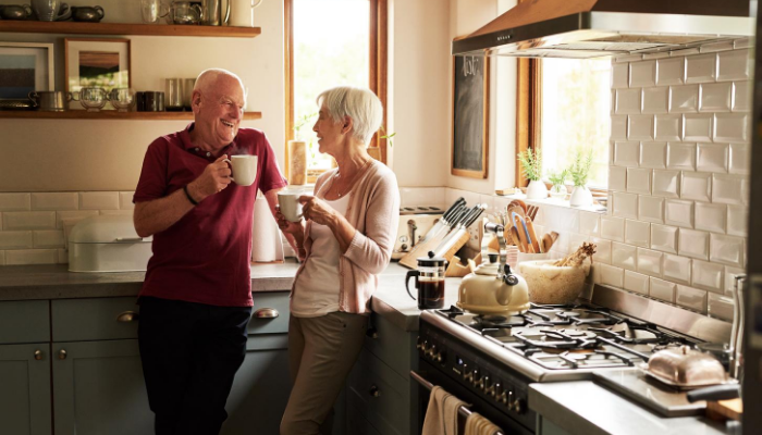 Older couple drinking coffee in house